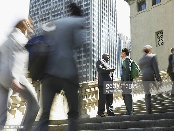 Two businessmen meeting on steps