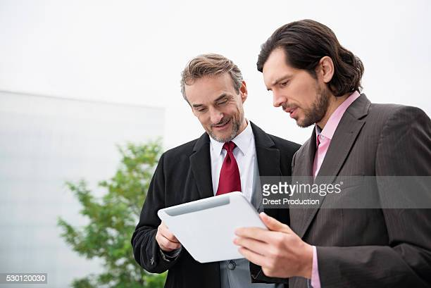 Two businessmen meeting Tablet PC planning realty