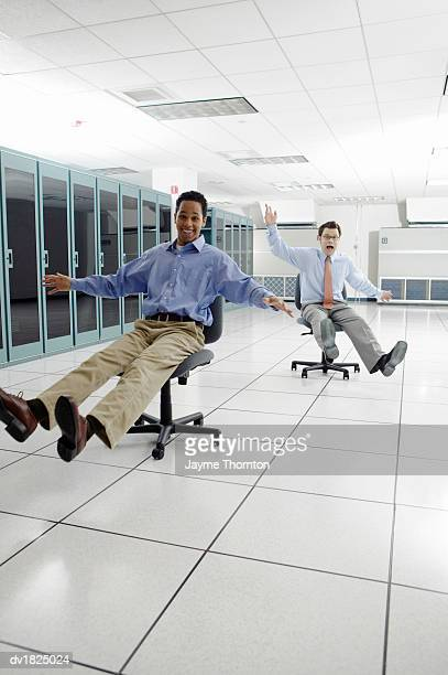 Two Businessmen Messing About on Swivel Chairs in an Office