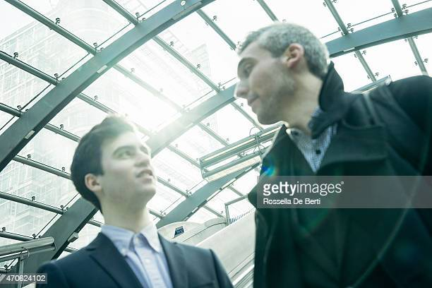 Two Businessmen On Escalator Getting In The Subway Station
