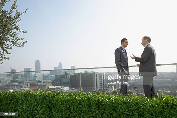 Two businessmen on rooftop talking, side view