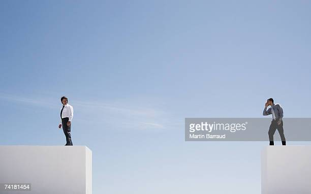 Two businessmen on walls outdoors with large gap