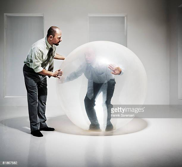 Two businessmen, one inside a balloon