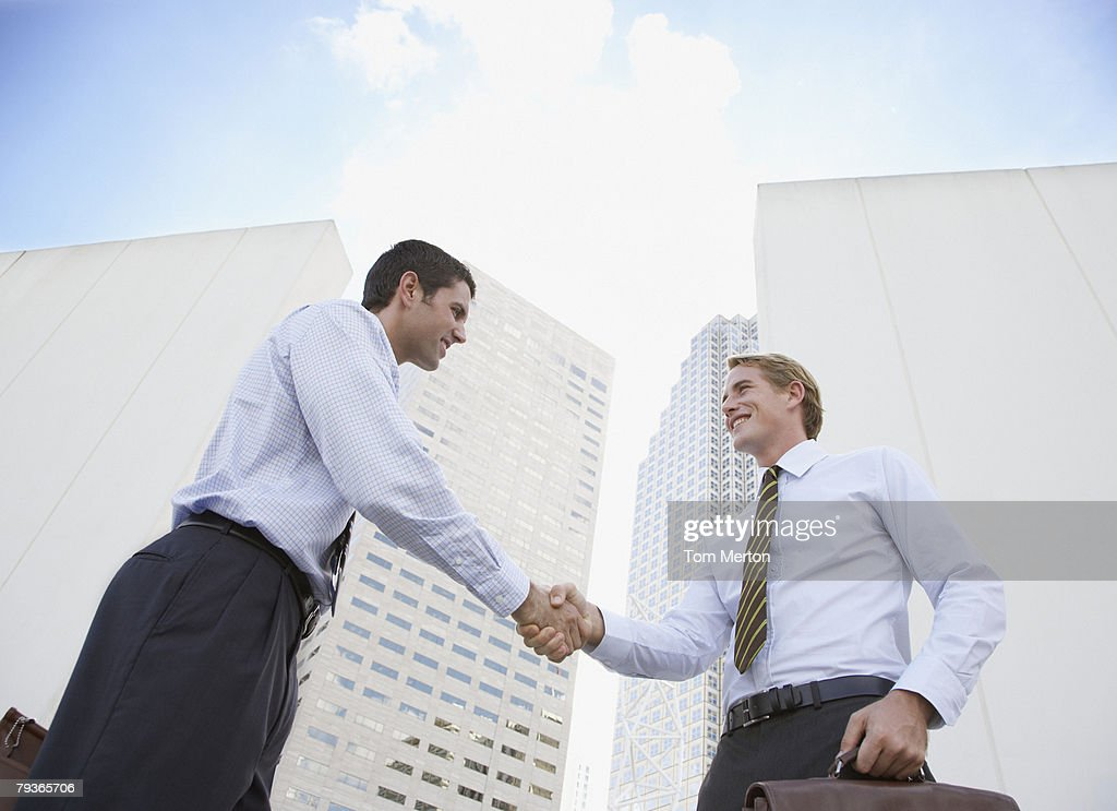 Two businessmen outdoors shaking hands : Stock Photo
