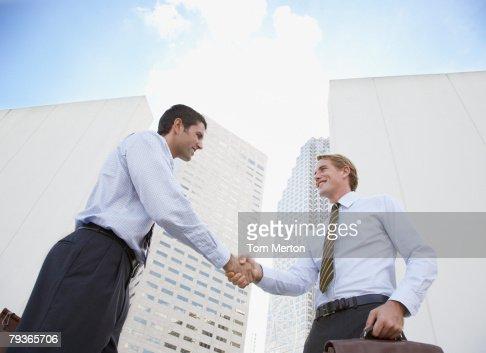 Dos hombres de negocios estrechándose las manos al aire libre : Foto de stock