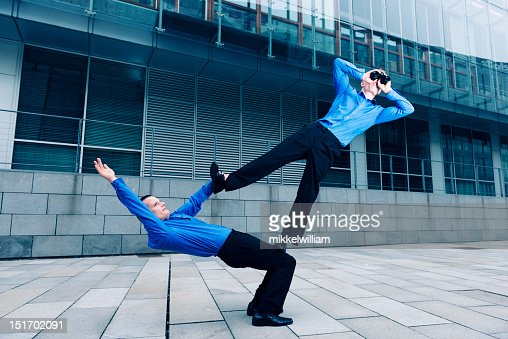 Two businessmen performing an acrobatic stunt together