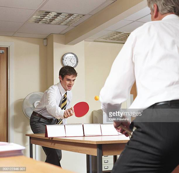 Two businessmen playing ping pong over desk