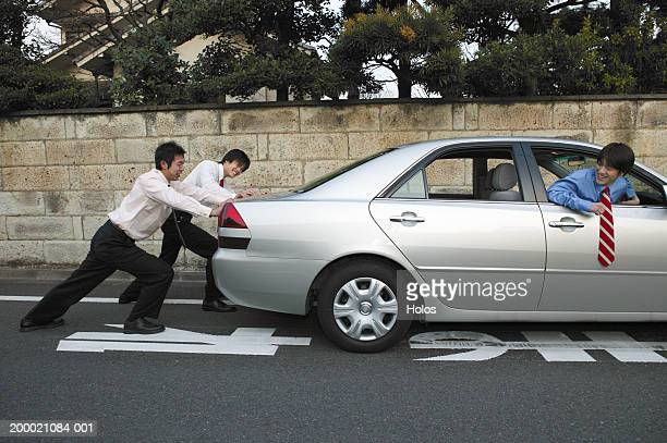 Two Businessmen pushing car