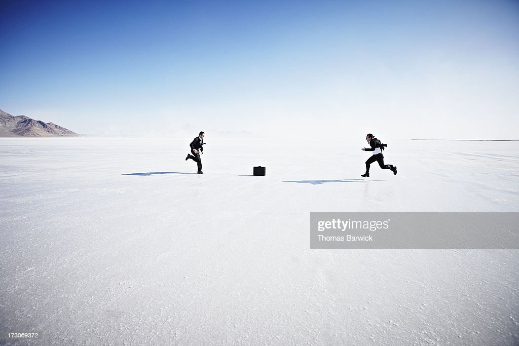 Two businessmen racing to pick up briefcase