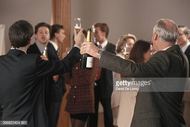 Two businessmen raising champagne