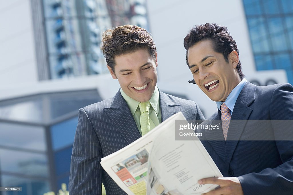 Two businessmen reading a magazine and smiling : Foto de stock