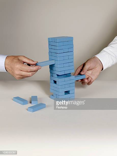 Two businessmen removing building blocks