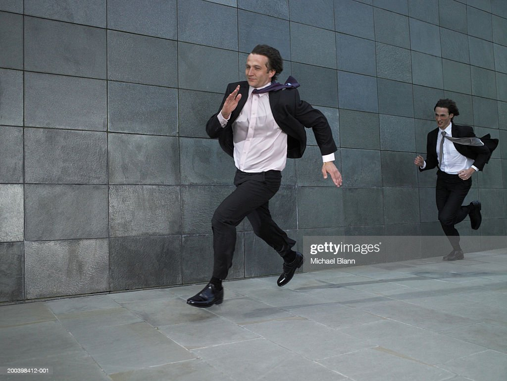 Two businessmen running against wind