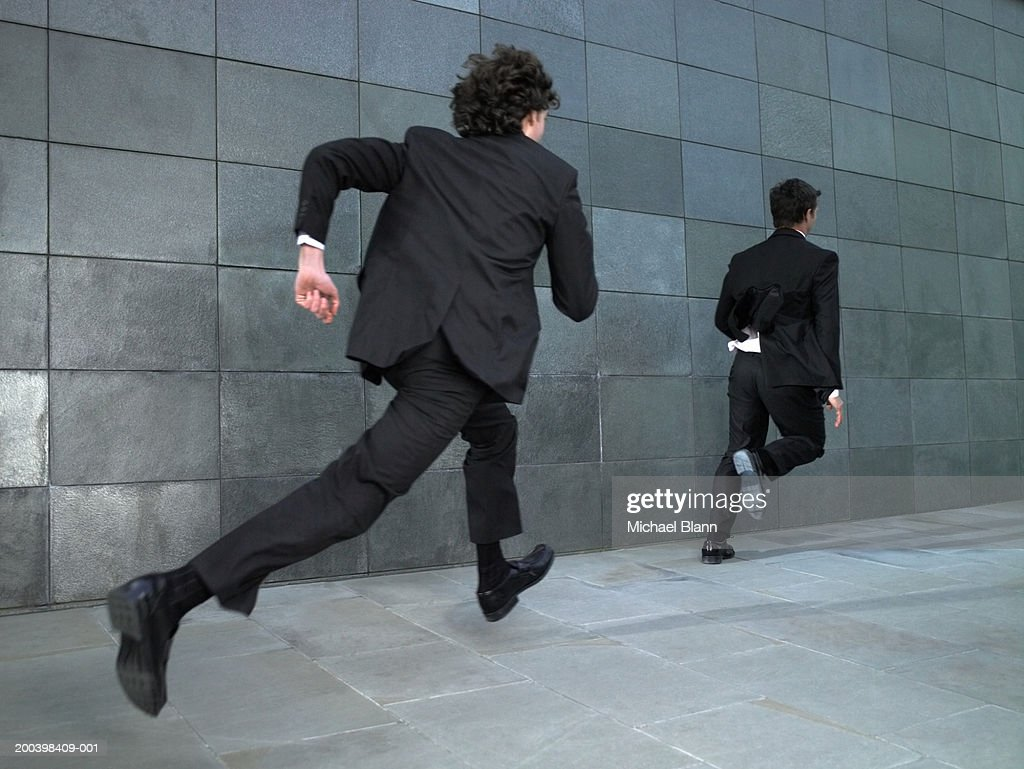 Two businessmen running along street, rear view : Stock Photo