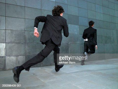 Two businessmen running along street, rear view