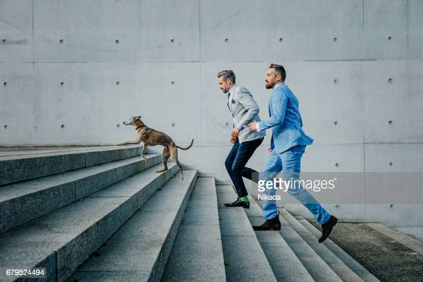 Two Businessmen running up on steps with dog