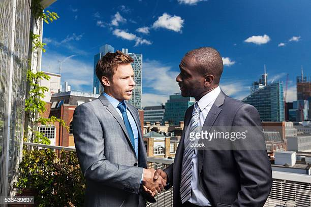 Two businessmen shaking hand outdoors