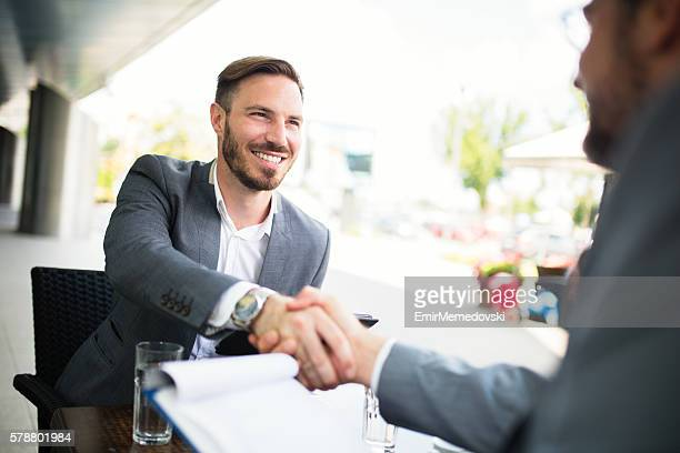 Two businessmen shaking hands after sealing the deal.
