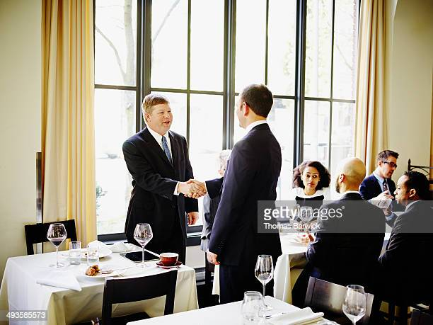 Two businessmen shaking hands at lunch meeting