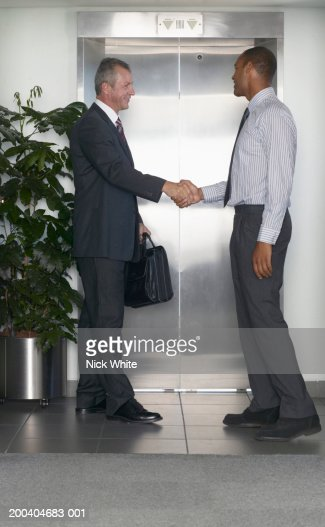 Two businessmen shaking hands by lift, side view : Stock Photo