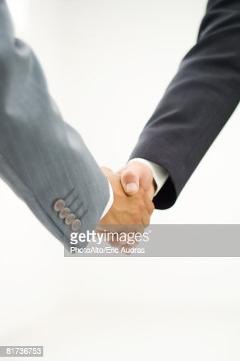 Two businessmen shaking hands, close-up, cropped view : Stock Photo
