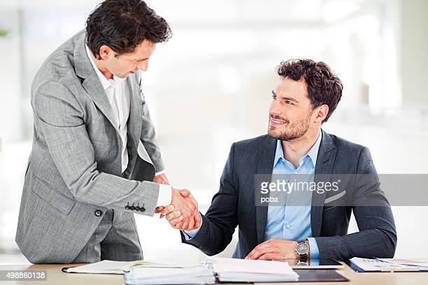 Zwei Geschäftsleute schütteln die Hände in boardroom