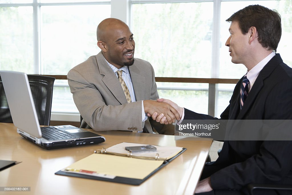 Two businessmen shaking hands in boardroom, smiling, side view