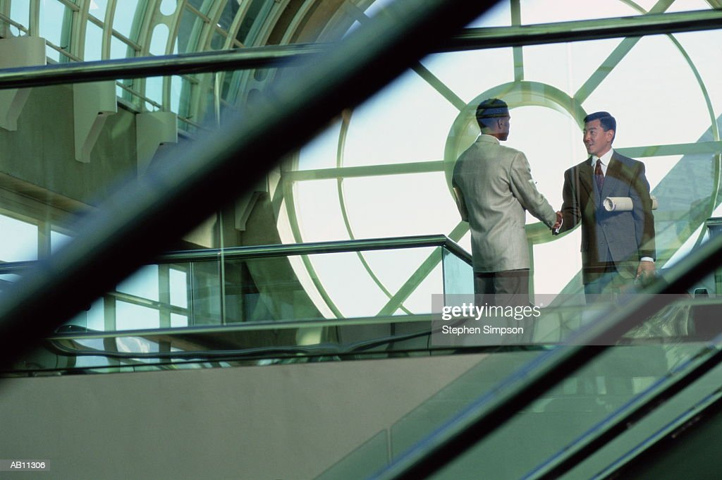 Two businessmen shaking hands in lobby : Stock Photo