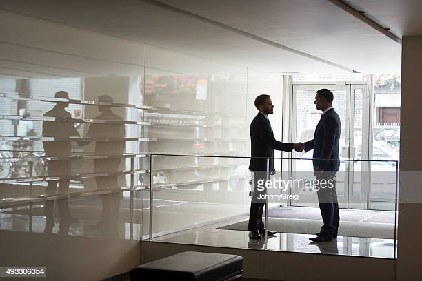 Two businessmen shaking hands in modern office, silhouette