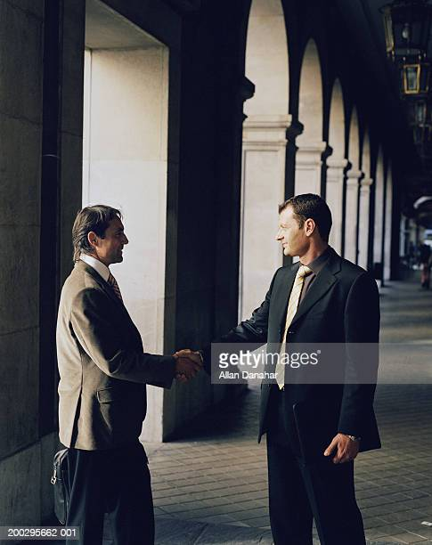 Two businessmen shaking hands on covered walkway