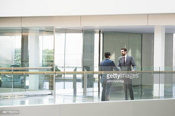 Two Businessmen Shaking Hands On Office Patio