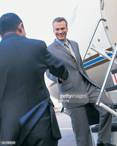 Two Businessmen Shaking Hands on the Boarding Bridge to a Corporate Jet