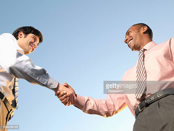 Two businessmen shaking hands (low angle view)