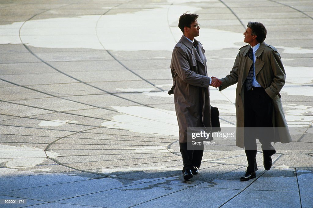 Two businessmen shaking hands, standing on world map : Stock Photo