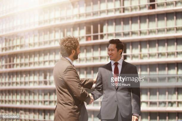Two businessmen shaking hands warmly in the city