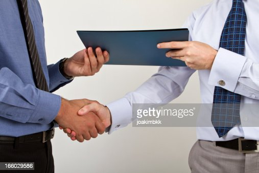 Two businessmen shaking hands with a document