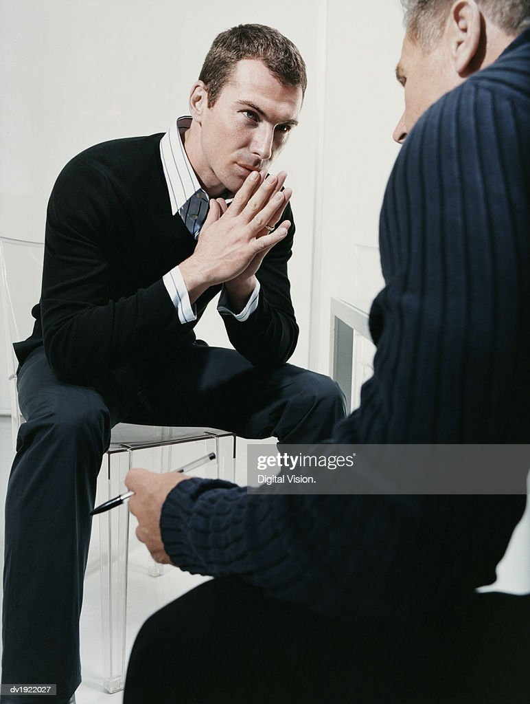 Two Businessmen Sit Face-To-Face in Serious Discussion