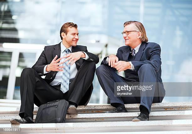 Zwei Geschäftsleute sitzen und Kommunikation.