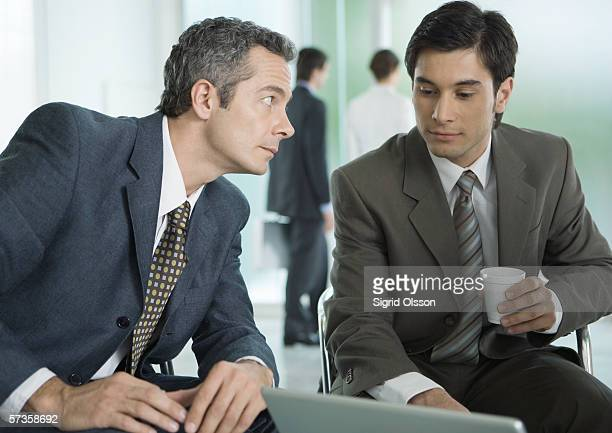 Two businessmen sitting around laptop, one with coffee cup