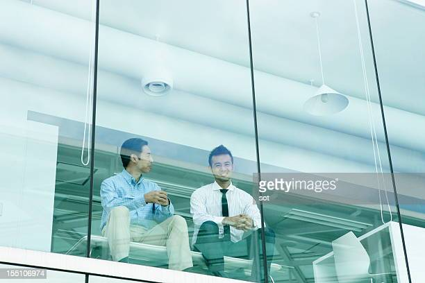 Two businessmen sitting at chair in office