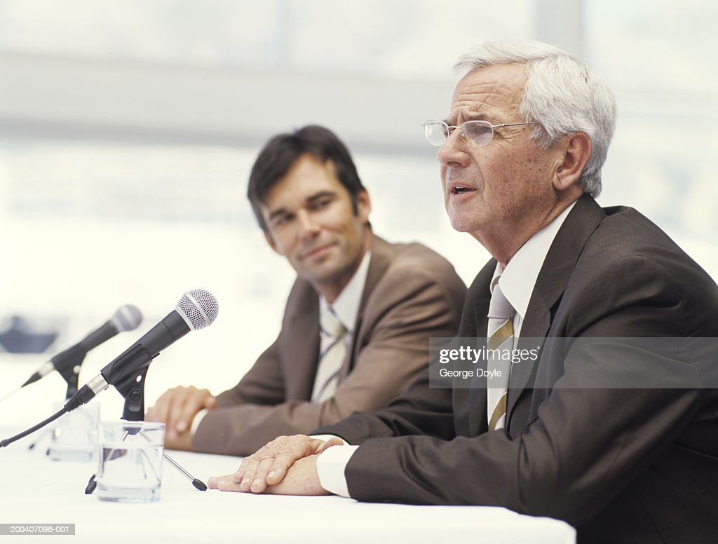 Two businessmen sitting by microphones, senior man speaking : Stock Photo