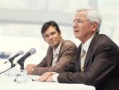 Two businessmen sitting by microphones, senior man speaking