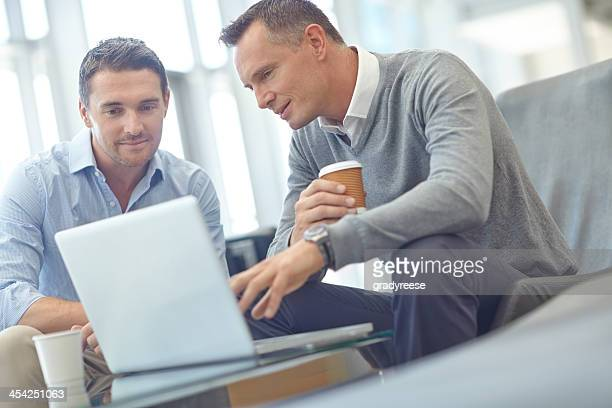 Two businessmen sitting in lounge with laptop