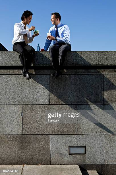 Two businessmen sitting on a wall during a lunch break