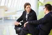 Two Businessmen Sitting On Sofa In Modern Office