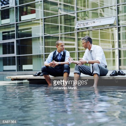 Two businessmen sitting outdoors, feet in pool of water : Stock Photo