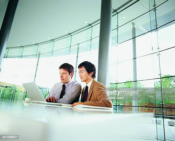 Two Businessmen Sitting Working on a Laptop in a Glass office