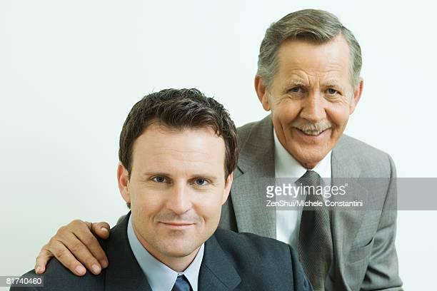 Two businessmen smiling at camera together, portrait