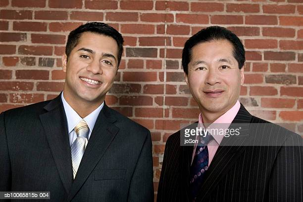 Two businessmen smiling, close-up, portrait