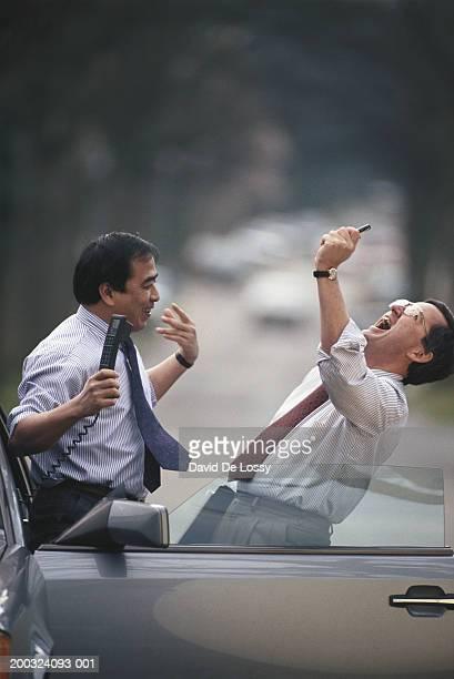 Two businessmen standing by car door, shouting